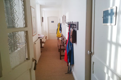 photo du couloir avec les porte manteaux et les affiches